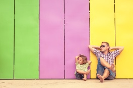 Father and son relaxing near the house at the day time. They sitting near are the colorful wall. Concept of friendly family.