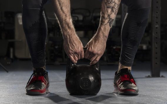 Closeup of muscular man doing a weight training by lifting a heavy kettlebell.Functional training.
