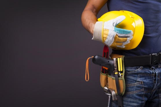 Close up of a worker with toolbelt and helmet against black background
